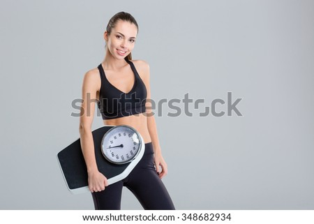 Beautiful smiling young fitness woman in tracksuit holding weigh scale over grey background - stock photo