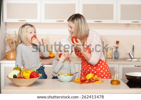 Beautiful smiling young mother and her two little daughters eating tomatoes while cooking salad. Kitchen interior. Concept for young kitchen hands