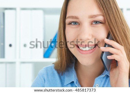 Beautiful smiling young secretary talking on the mobile phone looking into the camera.