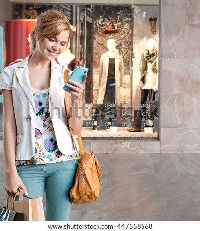 Beautiful smiling young tourist woman using a smart phone device to network, shopping in a shopping mall with fashion store window in background, technology and consumer lifestyle, city outdoors.