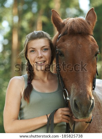Beautiful smiling young woman close-up with horse, against green of summer park. - stock photo