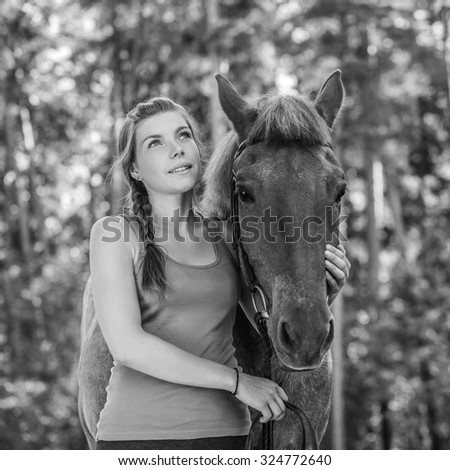 Beautiful smiling young woman close-up with horse, against green of summer park.