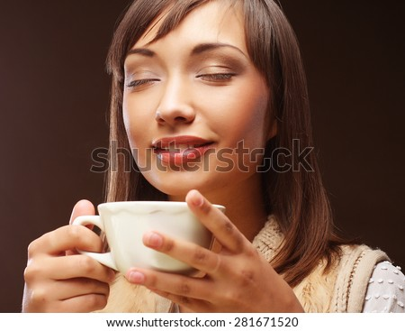 Beautiful smiling young woman drinking coffee over dark background - stock photo