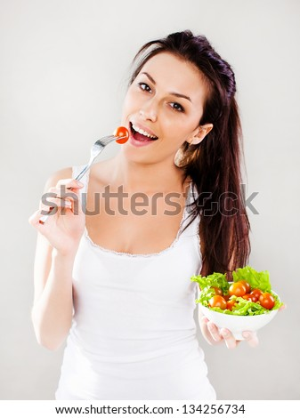 Beautiful smiling young woman eats vegetable salad. - stock photo