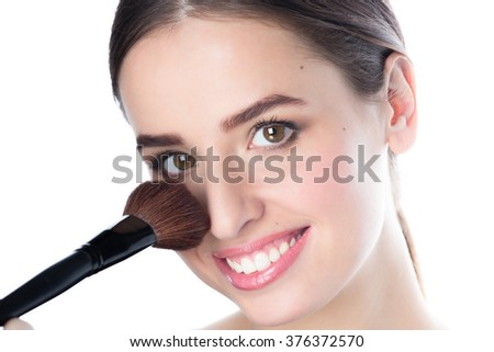 Beautiful smiling young woman holding a powder brush near her face, studio white