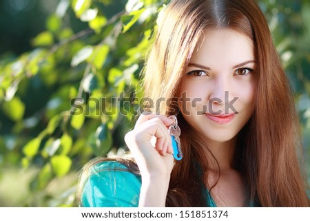 beautiful smiling young woman holding up a set of keys belonging to her house in her hand outdoor in green park  - stock photo