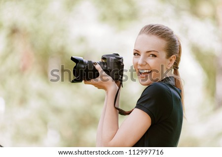 Beautiful smiling young woman in dark blouse photographs on camera, against green of summer park.