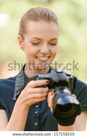 Beautiful smiling young woman in dark blouse photographs on camera, against green of summer park. - stock photo