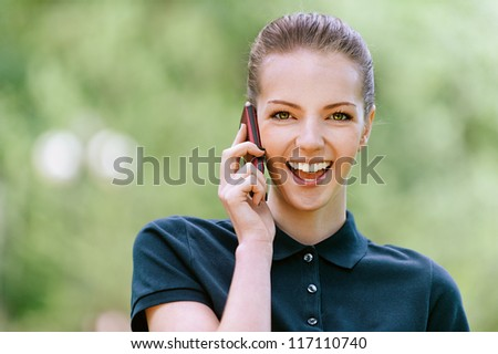 Beautiful smiling young woman in dark blouse talking on mobile phone, against green of summer park. - stock photo