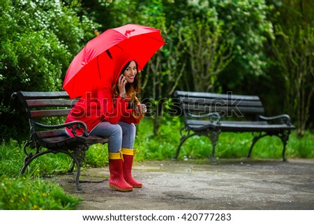 Beautiful smiling young woman in hooded red raincoat and rubber boots holding red umbrella. She is sitting on a bench in the park on a rainy day and talking on the phone while  looking at camera.