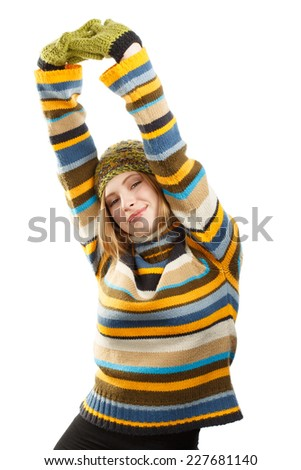 Beautiful smiling young woman in knitted striped sweater, hat and mittens stretching arms isolated on white background - stock photo