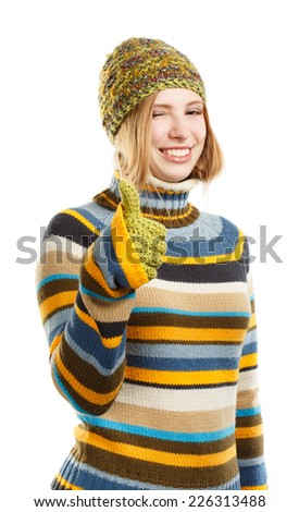 Beautiful smiling young woman in knitted striped sweater, hat and mittens with thumbs up gesture standing isolated on white background - stock photo