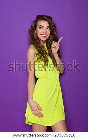 Beautiful smiling young woman in lime dress is pointing up and looking away. Three quarter length studio shot on purple background. - stock photo