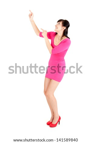 beautiful, smiling young woman in pink dress pointing up, full length, white background