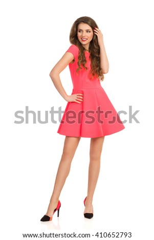 Beautiful smiling young woman in pink mini dress and high heels posing with hands on hip and looking away. Full length studio shot isolated on white.