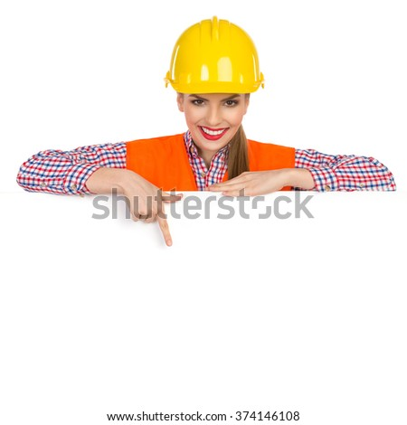 Beautiful smiling young woman in yellow hardhat, orange reflective vest and lumberjack shirt posing behind big white banner, pointing down and looking at camera. Studio shot isolated on white. - stock photo