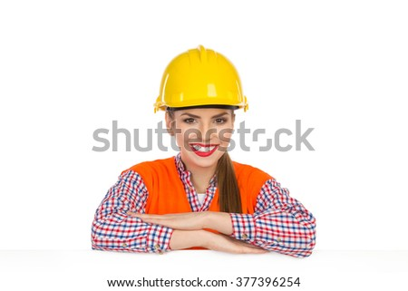 Beautiful smiling young woman in yellow hardhat, orange reflective vest and lumberjack shirt posing behind big white poster and looking at camera. Studio shot isolated on white. - stock photo