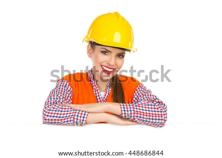 Beautiful smiling young woman in yellow hardhat, orange reflective vest and lumberjack shirt posing behind big white poster and looking at camera. Head and shoulders studio shot isolated on white. - stock photo