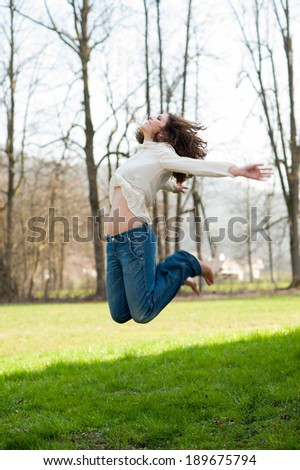 Beautiful smiling young woman jumping - stock photo