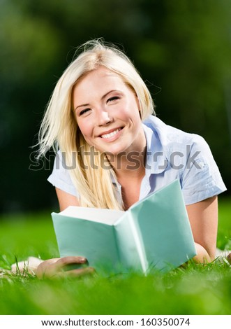 Beautiful smiling young woman lying on grass and reading book in the summer park