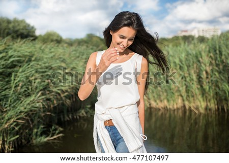 Beautiful smiling young woman on the lake background, on the nature background. Walking on the park. Travel. Vacation