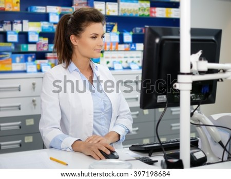 Beautiful smiling young woman pharmacist doing his work in pharmacy. - stock photo