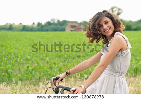 Beautiful smiling young woman portrait with bike in a country road. - stock photo