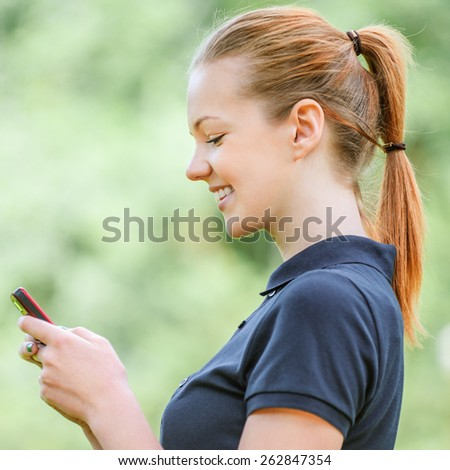 Beautiful smiling young woman profile in dark blouse talking on mobile phone, against green of summer park. - stock photo