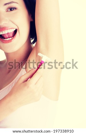 Beautiful smiling young woman shaving her armpit - stock photo