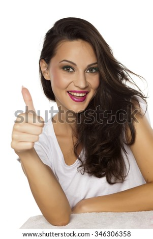 beautiful smiling young woman showing thumbs up - stock photo