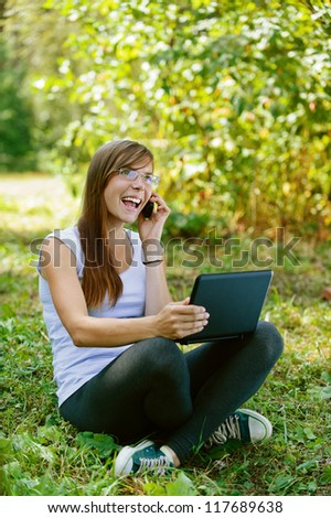 Beautiful smiling young woman sitting on grass with laptop and talking on mobile phone, against green of summer park.