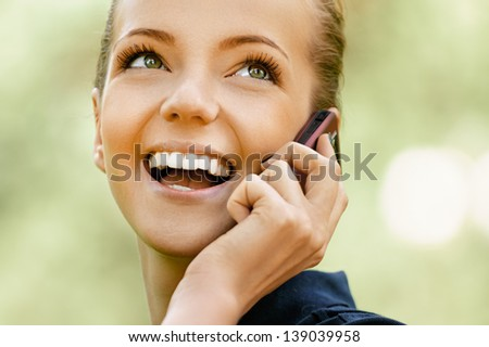 Beautiful smiling young woman talking on cell phone, against background of summer green park. - stock photo