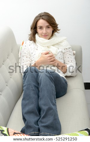 beautiful smiling young woman with a cup of tea in the sofa