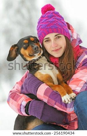 Beautiful smiling young woman with a dog in winter landscape.