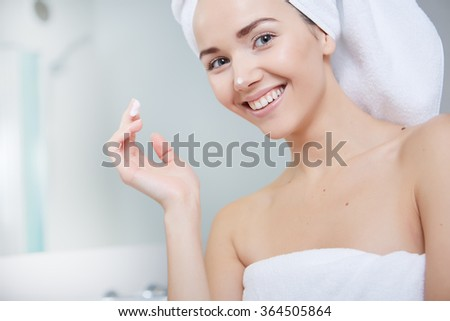 beautiful smiling young woman with a towel on her head after bath - stock photo