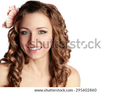 Beautiful Smiling Young Woman with Flower in her Long Curly Hair. Fresh Skin, Natural Looking Make up, Long Lashes. Isolated on White Background. Space for Text. - stock photo