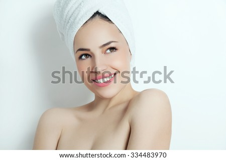 beautiful smiling young woman with healthy skin and towel on her head