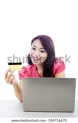 Beautiful smiling young woman with laptop and a credit card - stock photo