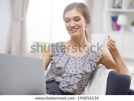 Beautiful smiling young woman with laptop and cup of coffee on the sofa
