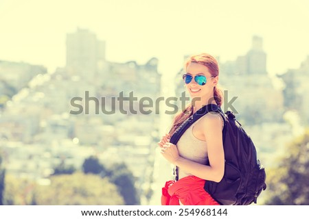 Beautiful smiling young woman with sunglasses and backpack in San Francisco city on a  sunny warm summer spring  day. Positive emotions face expression. Instagram style yellow filter image  - stock photo
