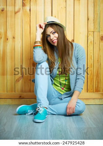 Beautiful smilingl girl sitting against wooden background on a floor. Youth teen style portrait.