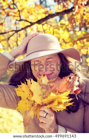 Beautiful smilling woman walking in the autumn park.
