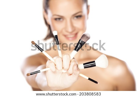 Beautiful smling woman with makeup brushes near her face