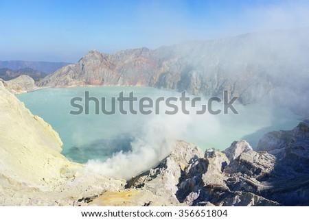 Beautiful smokey Kawah Ijen Volcano during blue sky in East Java island Indonesia. - stock photo