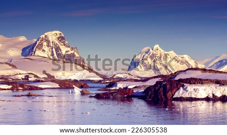 Beautiful snow-capped mountains against the sunset sky in Antarctica - stock photo