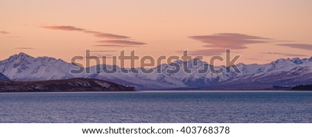 Beautiful snow-capped Southern Alps in New Zealand's South Island basking in sunset golden light in early spring, with the turquoise water of Lake Tekapo in the foreground