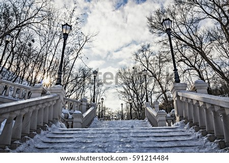 beautiful snow-covered stairway in the winter park with retro street lamps