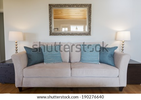 Beautiful sofa with blue pillows framed by modern light stands and mirrow in sumptuous style - stock photo