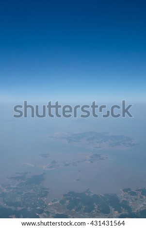 Beautiful soft background wallpaper of blue sky and land, view from airplane window. Top view of sea and blue sky, flying over South Korea.
