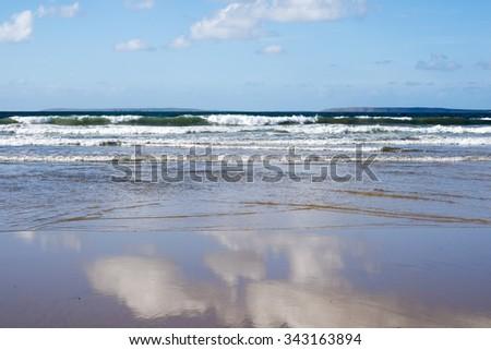 beautiful soft waves break on the sandy beach at ballybunion - stock photo